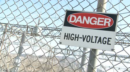 опасность : Danger Warning Sign on a fence with electrical industry in the background  Стоковые видеозаписи