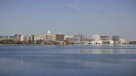управлять : Time lapse Skyline of Madison, Wisconsin with people fishing on the lake