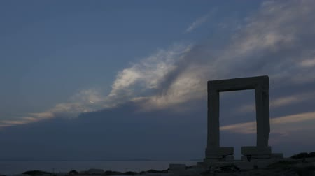 görögország : Time lapse of sunset behind the Portara gate, Naxos island, Greece during twilight and clouds passing by