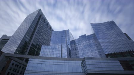 prospective : 4K Zoom in time lapse of perspective view to steel blue glass skyscrapers with clouds passing by, business concept of successful modern architecture with long exposures