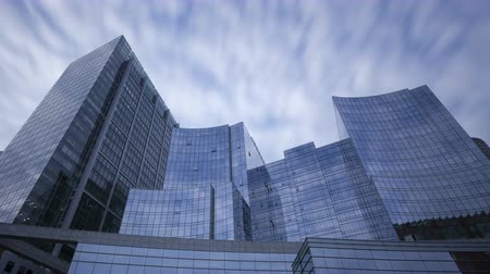 prospective : 4K Zoom out time lapse of perspective view to steel blue glass skyscrapers with clouds passing by, business concept of successful modern architecture with long exposures Stock Footage