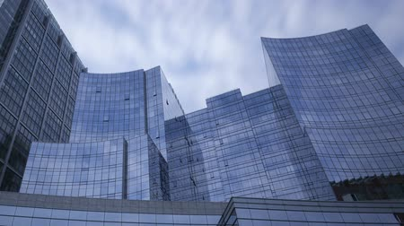 устойчивость : Tilt shot time lapse of perspective view to steel blue glass skyscrapers with clouds passing by, business concept of successful modern architecture with long exposures