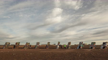 rota : AMARILLO, TEXAS, USA - JAN 28. 2015: 4K Time lapse zoom out, of people spraying graffiti at Cadillac Ranch, a public art installation and sculpture in Texas, U.S. close to historic Route 66