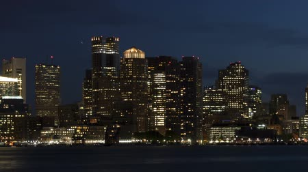 cambridge : Time lapse close up with a slow pan shot of Boston city skyline with clouds passing by at twilight with reflection of the skyscrapers over Charles River