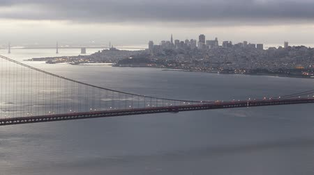 bay bridge : Time lapse sunrise Golden Gate Bridge close up pan shot with San Francisco downtown in the background and clouds passing by Stock Footage
