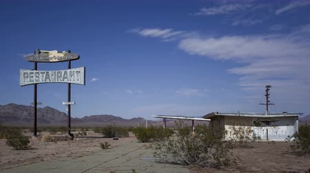 étkező : CHAMBLESS, CA, USA - MAY 24, 2014: 4K Time lapse close up of historic Road Runners Retreat diner ruin on Route 66 with a blue sky and clouds, near Chambless, California.