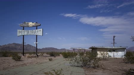 étkező : CHAMBLESS, CA, USA - MAY 24, 2014: 4K Time lapse zoom out of historic Road Runners Retreat diner ruin on Route 66 with a blue sky and clouds, near Chambless, California.