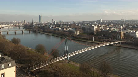Франкфурт : 4K Time lapse zoom out aerial view of the river Main in Frankfurt, Germany at daytime with boat traffic and people walking over the Holbeinsteg Bridge