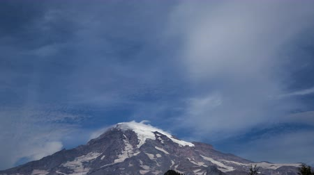 montar : 4K Time lapse of clouds zoom out passing the peak of Mount Rainier, Washington with a blue sky at daytime