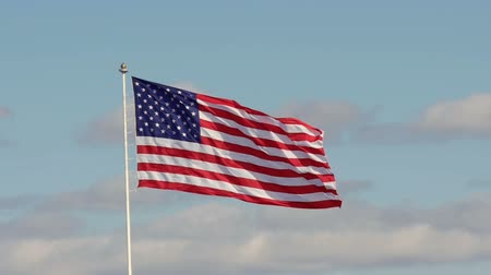 kutup : Slowmotion of US American flag waving in the wind with blue sky and clouds in the background