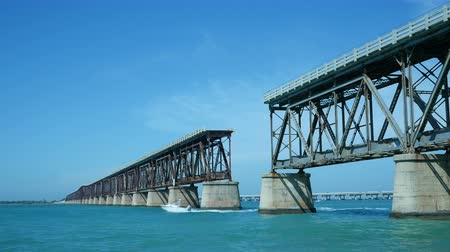 batı : Motor boat passes through historic broken Railroad Bridge at Bahia Honda State Park crossing the ocean between the islands.