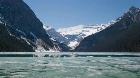 kanada : 4K Time lapse zoom out of Lake Louise in spring with broken ice on the surface. Lake Louise is one of the most visited lakes at Banff National Park, Alberta, Canada.