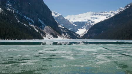kanada : 4K Time lapse pan shot of Lake Louise in spring with broken ice on the surface. Lake Louise is one of the most visited lakes at Banff National Park, Alberta, Canada.