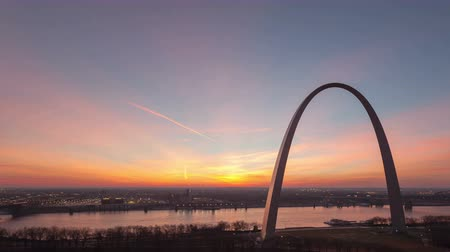 porta de entrada : 4K Time lapse aerial view St Louis Gateway Arch at sunrise with boat traffic on the river and red colored clouds