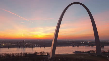 porta de entrada : Time lapse close up aerial view St Louis Gateway Arch at sunrise with boat traffic on the river and red colored clouds Vídeos