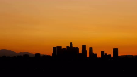 wschód słońca : 4K Time lapse tilt shot up sunrise over downtown Los Angeles skyline silhouette with red and orange colored sky Wideo