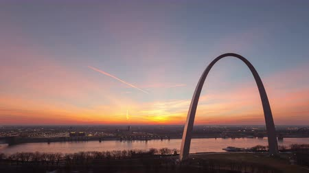 porta de entrada : 4K Time lapse tilt shot aerial view St Louis Gateway Arch at sunrise with boat traffic on the river and red colored clouds