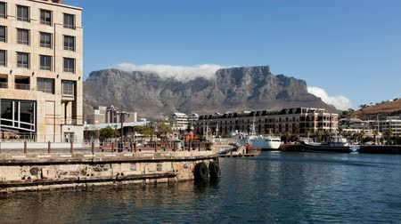 kasaba : CAPE TOWN, SOUTH AFRICA - MAR 16, 2010: 4K Time lapse wideangle Clouds over Table Mountain at daytime with Victoria and Alfred Waterfront on a sunny day