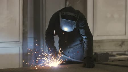 сварщик : The working welder processes the metal, prepares the base. A man in a protective suit, sparks.