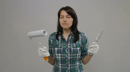 a woman looks at the paint brush and roller, screams in horror from the upcoming repair.