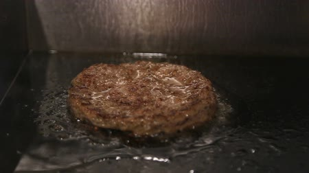 a burger pattu cutlet is fried on a hot, oiled stove