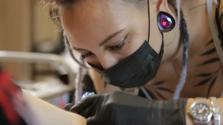 tattoo master girl stuffing a tattoo on her arm