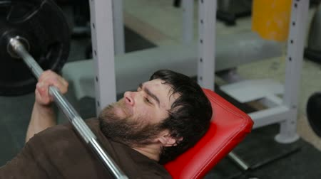 winda : powerlifter strogman picks up the bar lying on an incline bench