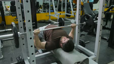 powerlifter : powerlifter strogman picks up the bar lying on the bench