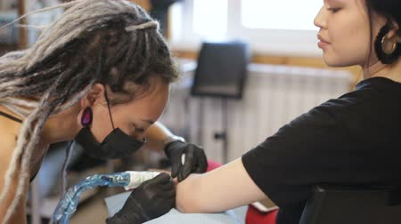 dolgok : tattoo master girl stuffing a tattoo on her arm
