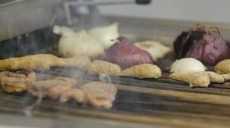 fritura : Selective focus woman hand holding stainless steel hot food gripping tong clamp frying meat and vegetable food on Grill at Seafood Restaurant. Archivo de Video