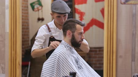 navalha : Master cuts hair and beard of men in the barbershop, hairdresser makes hairstyle for a young man