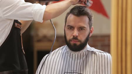 бритье : Master cuts hair and beard of men in the barbershop, hairdresser makes hairstyle for a young man