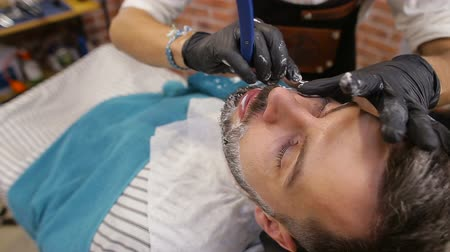 shaving foam : Bearded male sitting in an armchair in a barber shop while hairdresser shaves his beard with a dangerous razor