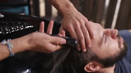 erkeklik : Profile view of a young arabic man getting his hair washed and his head massaged in a hair salon Stok Video