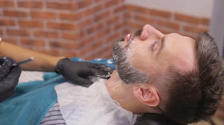 бритье : Bearded male sitting in an armchair in a barber shop while hairdresser shaves his beard with a dangerous razor
