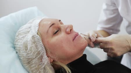 chirurgia estetica : Close-up of hands of cosmetologist making botox injection in female lips. Portrait of young caucasian woman getting cosmetic injection of botox. Filmati Stock