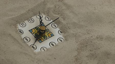 elusive : Clock with running second hand in the sand. The transience of time.