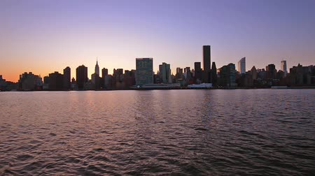 su üzerinde ufuk : New York City skyline on the east river at dusk. Stok Video