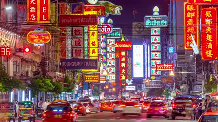 kínai negyed : BANGKOK, THAILAND - SEPTEMBER 27, 2015: Traffic on Yaowarat Road passes below lit signs in the Chinatown district at dusk. Stock mozgókép