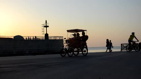Rimini, Italy - July 31, 2017: Pedaling in the harbor at sunset