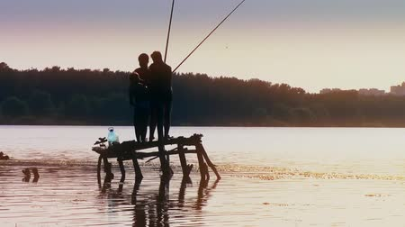 fenerbalığı : four boys fisherman fishing fish on wooden pier in lake at sunset forest on background new unique quality joyful people video footage