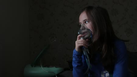 oksijen : Inhalation Sick Girl With Nebulizer In The Living Room Child with inhalation mask and inhaler.  Girl, 10 years old, using nebulizer to inhale medicine. Stok Video