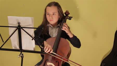 cselló : Young Girl Playing Violoncello Looking At The Notes Cellist Soloist In her room. Background is yellow wall