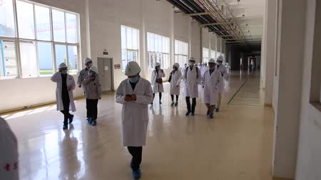 eixo : An excursion to the factory, people in White robes go through the factory workshop, which makes transformers Stock Footage