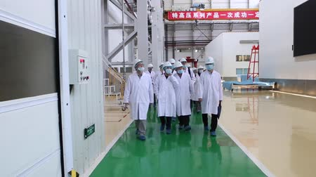 axle : An excursion to the factory, people in White robes go through the factory workshop, which makes transformers Stock Footage