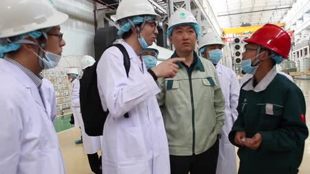 power plant : An excursion to the factory, people in White robes go through the factory workshop, which makes transformers Stock Footage