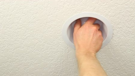 régi : Hand of a man changing an old incandescent light bulb with a newer daylight white compact fluorescent lightbulb to save energy.