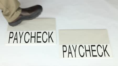spent : Person stepping from one paycheck to another paycheck to illustrate the phrase living paycheck to paycheck.