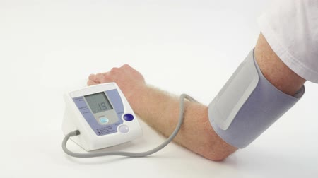 choroba : Man seen measuring his own blood pressure on a digital blood pressure monitor. Wideo