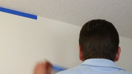 trabalhador manual : Man preparing to paint a white ceiling by masking off the wall beneath it with blue painters tape. Vídeos